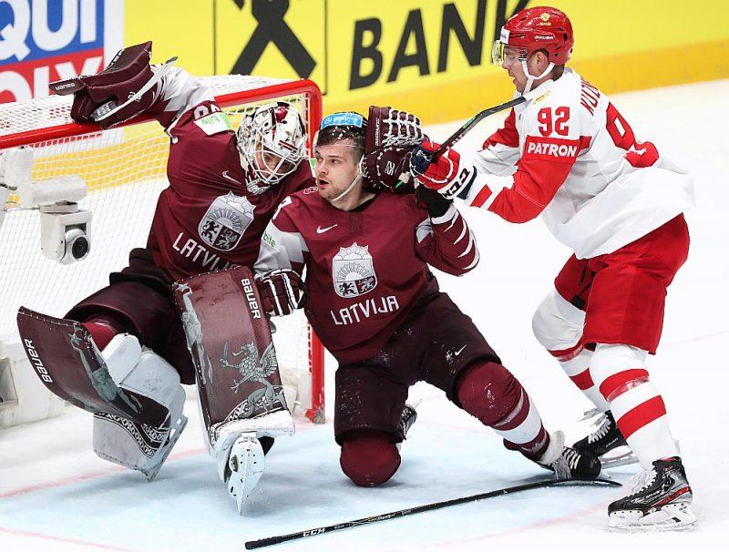 Teodors Bļugers (centrā) pasaules čempionāta spēlē pret Krievijas izlasi saķēries ar Jevgeņiju Kuzņecovu, vārtos – Elvis Merzļikins, kurš par Latvijas Gada hokejistu tika atzīts pērn.