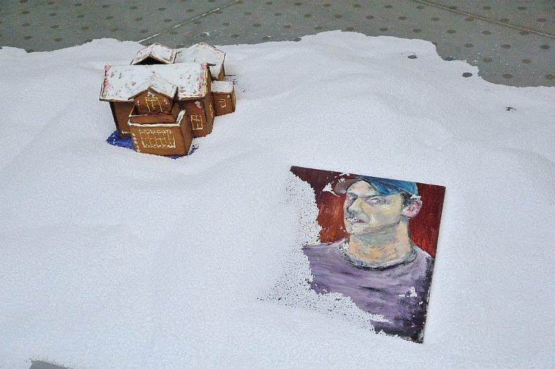 """Telpā pirms lielās zāles izkārtota egle un izbērts sniegam līdzīgs materiāls ar """"piparkūku"""" mājiņu."""