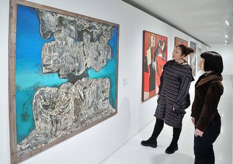 """Interese par Džemmas Skulmes darbiem pēc mākslinieces aiziešanas mūžībā aizvien aug. Fonā: darbs """"Kara kariatīdes"""" (1976. gads) no Latvijas Nacionālā mākslas muzeja krājuma. No kreisās – izstādes """"Džemma Skulme. Viņas glezniecība"""" kuratore Inga Šteimane un muzeja pārstāve Natālija Sujunšalijeva."""