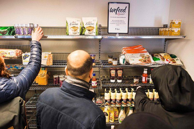 """Ļaudis iepērkas Kopenhāgenas """"Wefood"""" lielveikalā, kurā pēc termiņa beigām pārdod preces ar norādi """"vislabāk izlietot līdz"""". Visas preces par 5 kronām (67 centiem)."""
