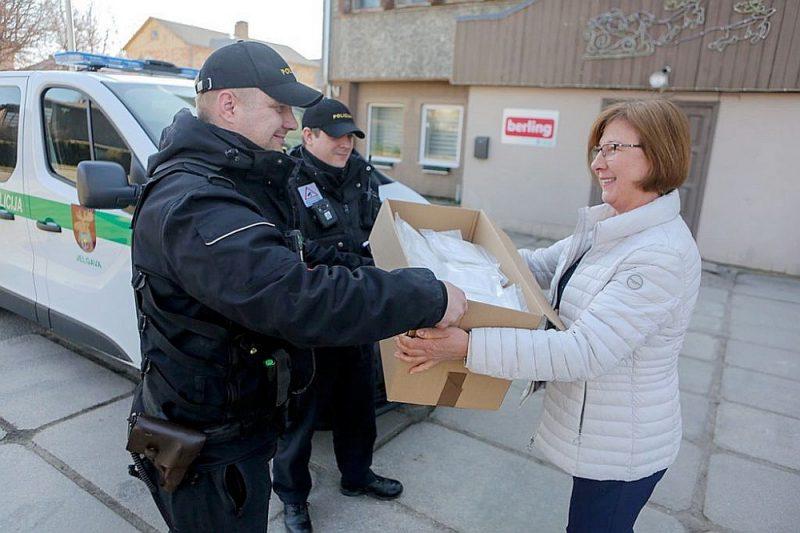 """Jelgavas uzņēmuma """"Berling"""" darbiniece nodod saražotās sejas maskas Jelgavas policijas pārstāvjiem."""