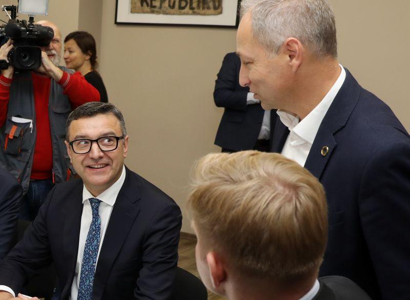 """Daži koalīcijas parstāvji JKP un NA vienošanos uztver kā """"sveicienu"""" finanšu ministram Jānim Reiram (""""Jaunā Vienotība""""), kurš iepriekš nav ļāvis tērēties iecerētajiem projektiem."""