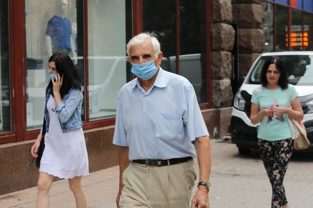 Vīrietis uz ielas ar sejas masku.