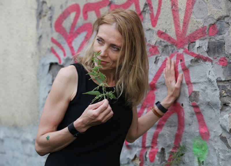 Ilze Burkovska-Jakobsena tepat Dzirnavu ielā pie apzīmēta brandmūra ar kupli sazaļojušām nātrēm, no kurām viņa nevairās – liekot gan Jāņu zāļu pušķī, gan savam dārzam brūvējot bagātīgu mēslojumu.