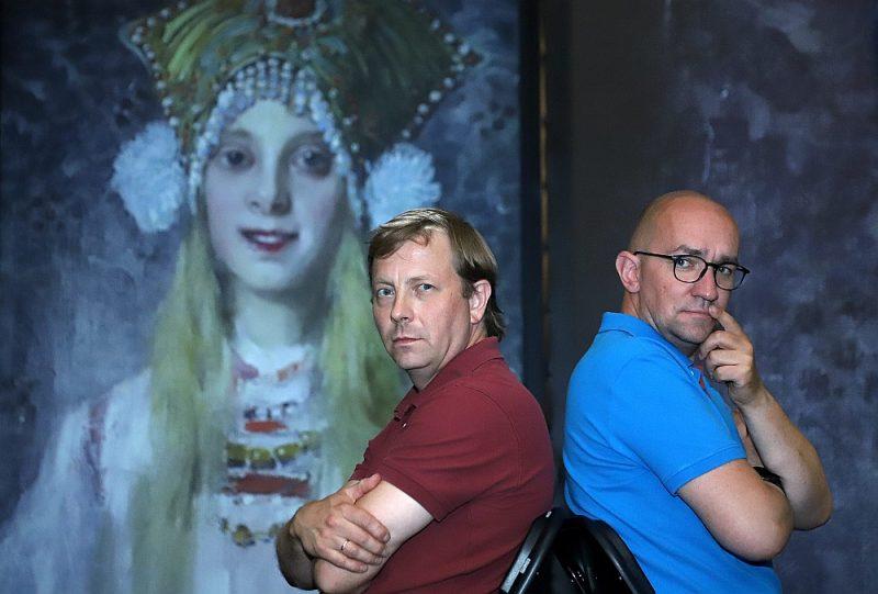 """Renārs Sproģis (no labās) kopā ar līdzproducentu Ivo Valdovski Cēsu Pilsmuižas klētī izveidojis neparastu multimediju izstādi """"Simbolisms"""", kas jaunās krāsās, skaņās un kustībā atklāj vairāk nekā 40 spilgtākos latviešu vecmeistaru darbus. Attēla fonā: Jaņa Rozentāla glezna """"Laila kokošņikā"""". 1913. g. Privātkolekcija."""