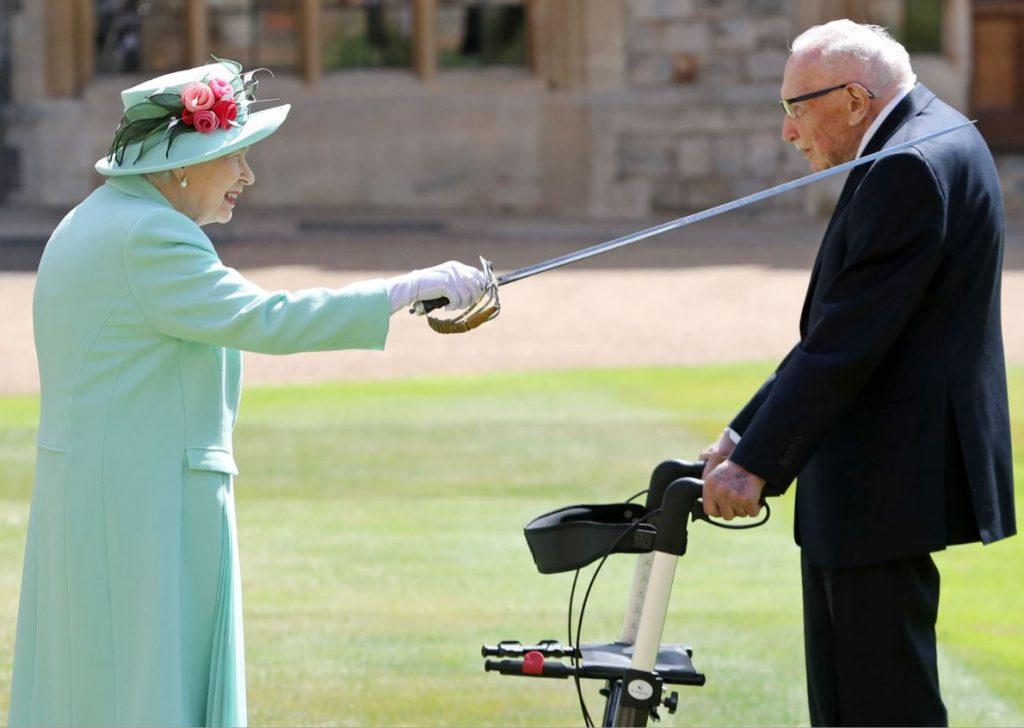 Karaliene Elizabete II bruņinieka kārtā ieceļ 100 gadīgo Tomu Mūru.