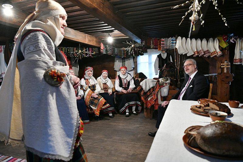 """Valsts prezidents Egils Levits pirms likuma iniciatīvas iesniegšanas Saeimā šogad devās vairākās vizītēs uz Latvijas kultūrvēsturiskajiem novadiem, kur, tiekoties ar iedzīvotājiem, arī runāja par identitātes jautājumiem. Attēlā: šā gada martā E. Levits viesojās Rucavā un tikās ar tradicionālā mantojuma kopējiem """"Zvanītājos""""."""