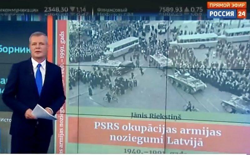 """""""Rossija 24"""" raidījuma """"Vesti"""" vadītājs Aleksejs Kazakovs neizpratnē par Rīgā izdoto grāmatu."""