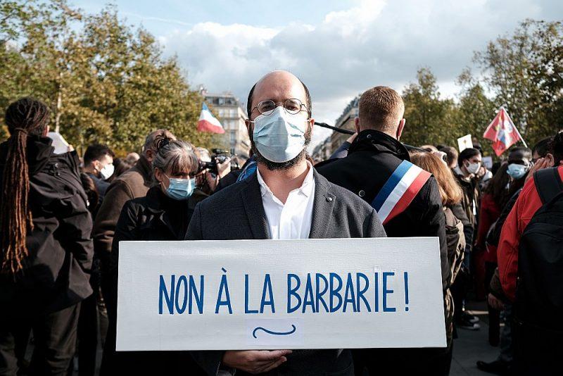 """""""Nē barbarismam!"""" aicina pagājušajā svētdienā Parīzē un arī citās Francijas pilsētās sarīkoto skolotāja Samuela Patī piemiņas demonstrācijas dalībnieks."""