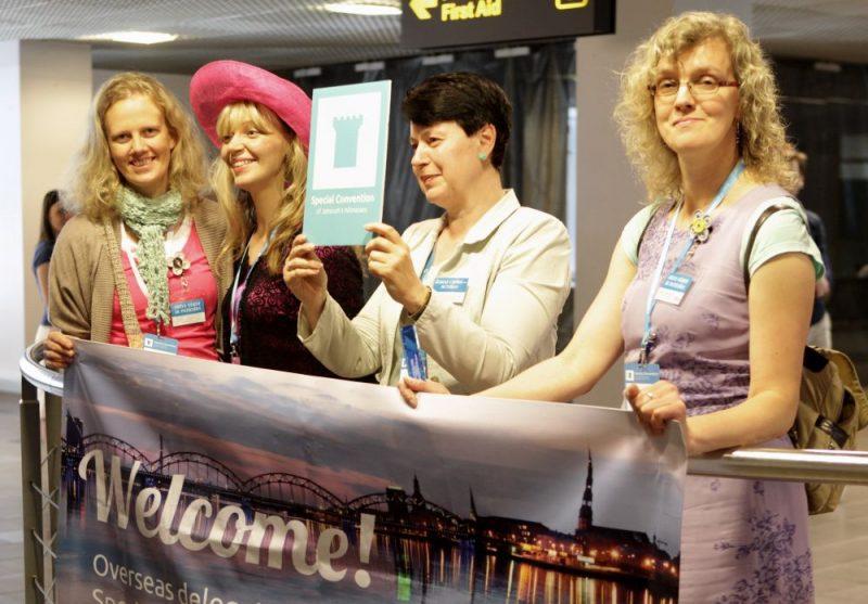 """Jehovas liecinieku pārstāvji Rīgas lidostā sagaida ierodamies delegātus uz Jehovas liecinieku kongresu """"Dieva vārdi ir patiesība"""" 2013.gadā."""