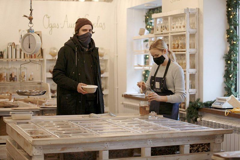 """Par pastāvīgu """"Burkas"""" apmeklētāju kopš 2019. gada kļuvis netālu dzīvojošais students Kristers Ozoliņš (no kreisās). Attēlā: veikala pārdevēja Kristeram palīdz sasvērt produktus."""