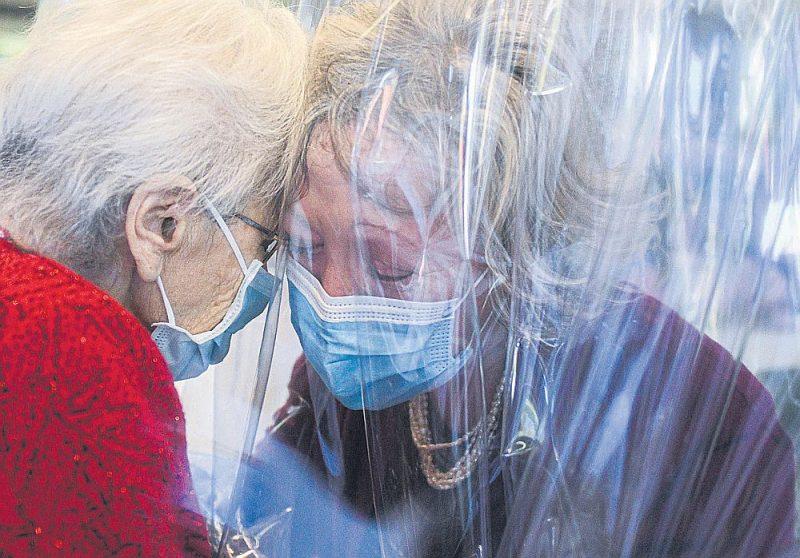"""Saslimstība ar Covid-19 ir liela problēma veco ļaužu aprūpes namos visā pasaulē. Pansionātos noteikto ierobežojumu dēļ seniori nevar satikt savus tuviniekus, tāpēc daudzviet atrod risinājumus, kā to izdarīt, mēģinot izvairīties no inficēšanās. Attēlā: kāda pansionātā Venēcijā (Itālija) māte ar meitu apskaujas caur polietilēna plēvi tā sauktajā """"Apskāvienu istabā""""."""